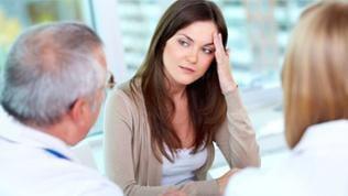 Eine Junge Frau sitzt vor zweit Ärzten und fasst sich an den Kopf