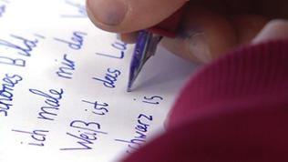 Ein Kind schreibt mit einem Füller auf ein Stück Papier
