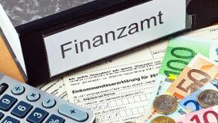 """Ein Ordner mit der Aufschrift """"Finanzamt"""". davor liegen Geld, ein Taschenrechner und ein Formular zur Steuererklärung"""