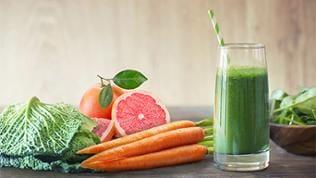 Ein grüner Smoothie, Zutaten liegen daneben: Grünkohl, Karotten, Grapefruit und Spinat