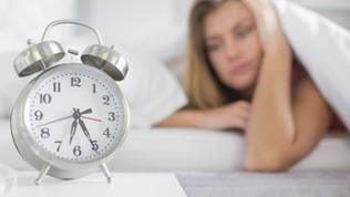 Eine Frau starrt auf ihren Wecker
