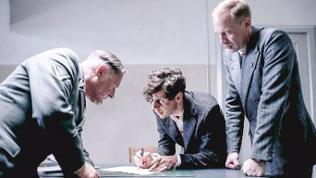 zwei Männer verhören einen Dritten, der an Tisch sitzt