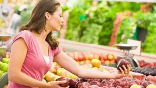 Eine Frau beim Einkaufen, sie hält einen roten Apfel in der Hand und begutachtet ihn.