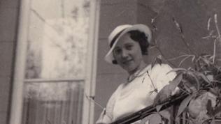 eine Frau mit hellem Hut steht an einem Treppengeländer