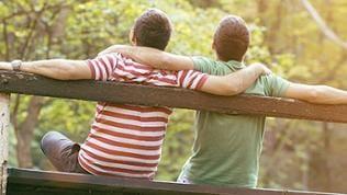 Zwei Männer sitzen entspannt auf einer Bank im Park und umarmen sich.