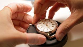 Hände halten das Zifferblatt einer Uhr