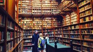 Abt zeigt zwei Mädchen Bibliothek im Kloster Maria Laach