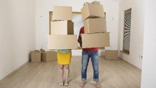 Ein Paar steht in einer Wohnung mit Umzugskisten in den Händen