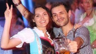Eine Frau und ein Mann in Tracht prosten mit einem Glas Bier in die Kamera