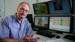 Meteorologe Sven Plöger vor einer Reihe Monitore sitzend, die Wetterdaten und -karten anzeigen