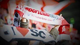 Ein Freiburger Fan hält seinen Schal im Stadion hoch.