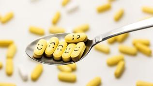 Tabletten, mit aufgemalten Smiley-Gesichtern liegen auf einem Löffel.