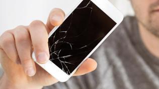 Ein Man hält ein defektes Smartphone
