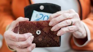 Eine ältere Frau mit Geldbeutel