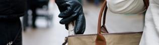 Ein Mann greift in die Handtasche einer Frau und klaut den Geldeutel