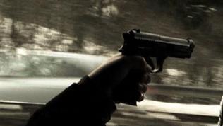 eine Hand hält eine Pistole im Auto