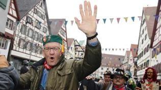 Ministerpräsident Winfried Kretschmann zieht fröhlich mit Hunderten Narren durch die Altstadt in Riedlingen und grüßt in die Kamera.