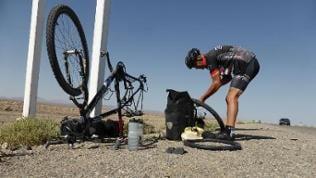 Ein Mann repariert am Straßenrand einen Fahrradschlauch