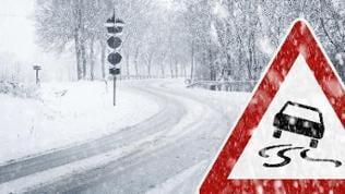 Ein Schild warnt vor Rutschgefahr, im Hintergrund ist eine stark verschneite Strasse zu sehen.