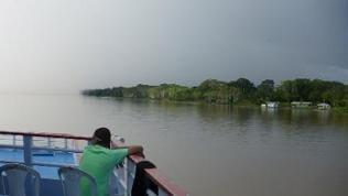 Eine Regenwand nähert sich: Im Vordergrund der Amazonas, im Hintergrund der Regenwald