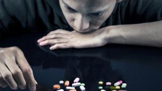 Ein Junge ist zu sehen, im Vordergrund sind Pillen verstreut.