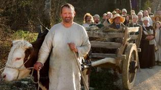 Die Stammmannschaft von Meßkirch in mittelalterlichen Gewändern zieht hinter einem vom Ochsen gezogenen Karren auf die Baustelle