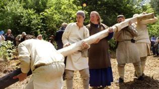 Männer in mittelalterlichen Gewändern errichten auf der Klosterbaustelle in Meßkirch  ein Holzkreuz