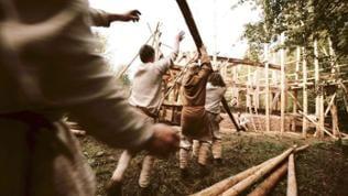 Handwerker stellen gemeinsam einen Balken für die Holzkirche auf