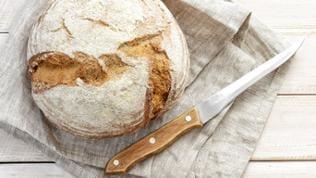 Ein Brot und ein Messer liegt auf einem Tisch