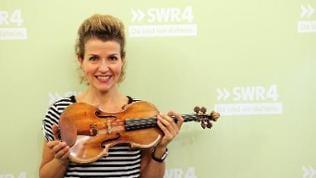 Anne-Sophie Mutter steht mit ihrer Geige vor einer grünen SWR4 Wand