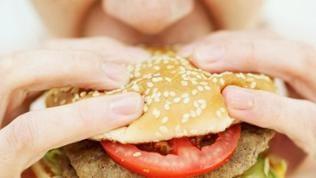 Eine Frau beißt in einen Hamburger
