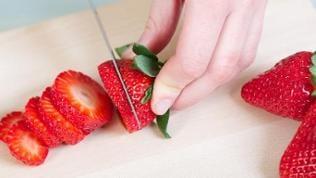 Eine Frau schneidet Erdbeeren auf.