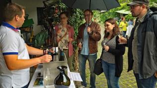 Besucher bei Regenwetter bei der Weinverkostung
