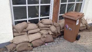 Braune dreckige Sandsäcke liegen vor einer Terrassentür, daneben steht eine braune Mülltonne