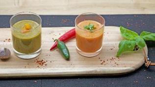 zwei gläser auf einem Brett mit grüner und roter soße mit chilis und basilikum als deko