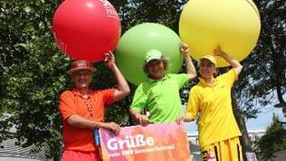 Drei Personen auf Stelzen mit Luftballons und einem Schild mit Grüße