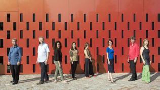 Gruppenbild Ensemble Experimental vor rotem Haus mit vielen kleinen Fenstern