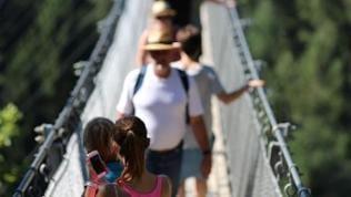 Eine junge Frau macht auf der Hängeseilbrücke ein Selfie