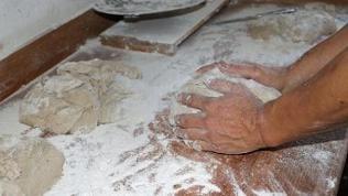 Teig auf Tischplatte aus Holz mit viel Mehl drumherum, zwei Hände kneten den Teig, nah