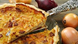 Ein Zwiebelkuchen wird mit einem Tortenheber angehoben.