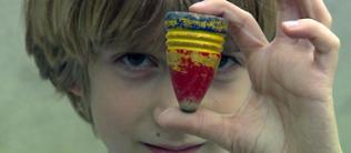 Kind hält sich rot-gelb-blauen Holzkreisel vors Gesicht