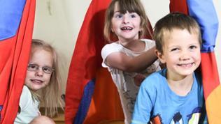 Drei Kinder sitzen in einem Spielzelt
