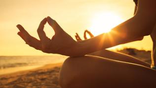 Frau macht im Sonnenuntergang Yoga