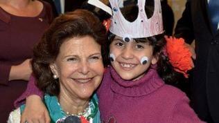 Die schwedische Königin Silvia mit einem Flüchtlingskind