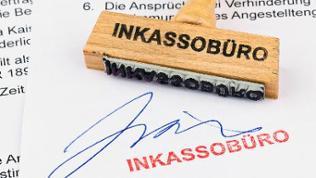 Auf einem Blatt Papier wurde das Wort Inkassobüro mit einem Holzstempel aufgedruckt.