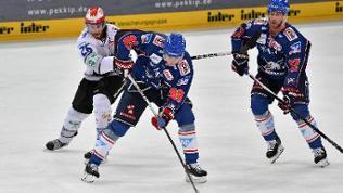 Eishockey-Zweikampf zwischen Jake Hansen (Schwenninger Wild Wings, l.) und David Wolf (Adler Mannheim, m.)