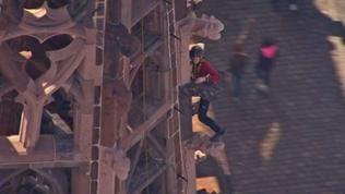 Steinmetzin arbeitet gesichert auf einem Turm