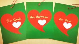 Drei grüne Hochglanzkarten mit roten Herzen darauf