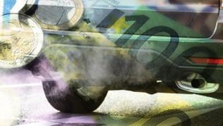 Abgase strömen am 14.11.2016 in Stuttgart (Baden-Württemberg) während eines Feinstaubalarms aus dem Auspuff eines Autos. Darüber liegen Geldscheine