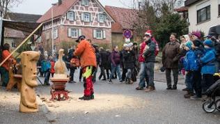 Ein Kettensägenkünstler schnitzt eine Holzfigur